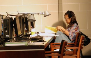 a person sitting on the computer desk with pile of notes