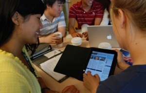 students working in groups with an ipad
